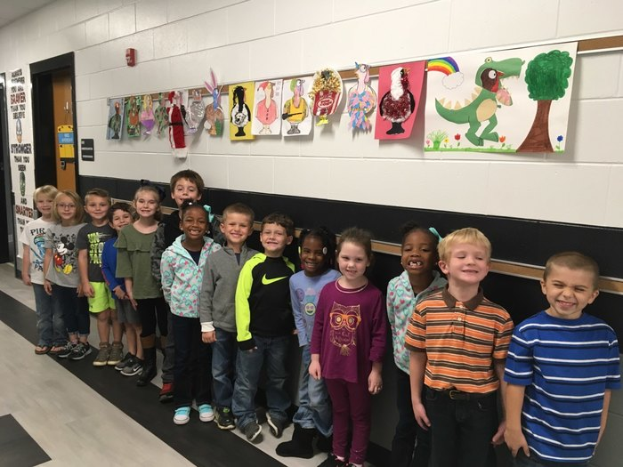 Students pose with artwork.