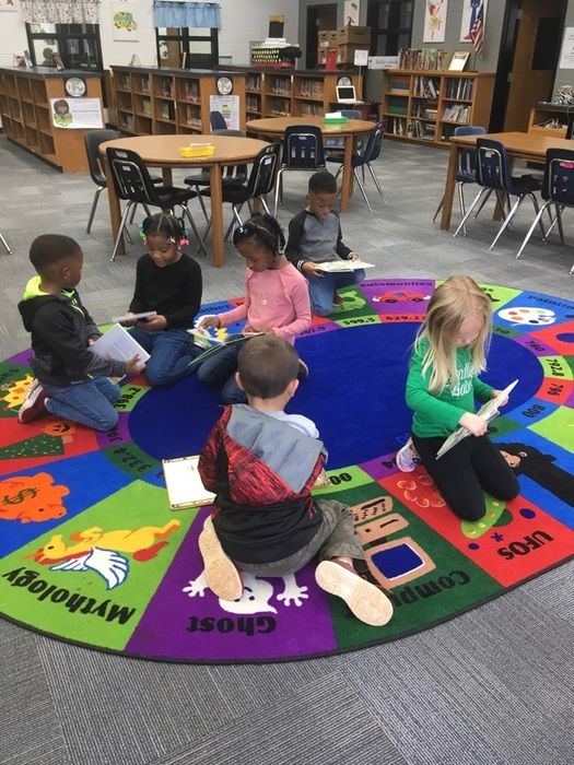 Kindergarten students look at their library books.